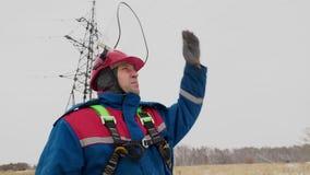 Casco aperto dell'uomo dell'elettricista e guardare intorno sul campo di neve archivi video