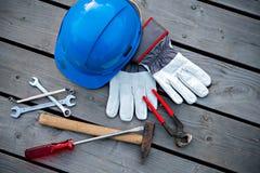 Casco azul, diversas herramientas y guantes del trabajo Fotos de archivo