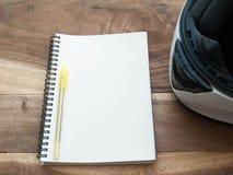 Casco blanco y libro blanco en la tabla de madera vieja Foto de archivo libre de regalías