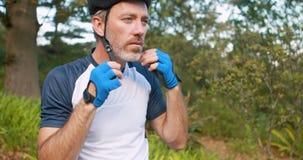 Casco d'uso del ciclista maschio alla campagna stock footage