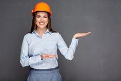 Casco d'uso del costruttore della donna che presenta le mani vuote Fotografie Stock