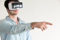 Casco d'uso del vr del giovane che mostra o che tocca gli oggetti virtuali immagine stock libera da diritti