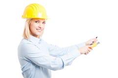 Casco d'uso dell'architetto femminile facendo uso dello strumento della taglierina immagine stock libera da diritti