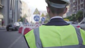 Casco d'uso dell'attrezzatura e del costruttore di sicurezza del ragazzino che cammina su una strada di grande traffico in una gr stock footage