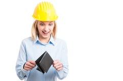 Casco d'uso dell'ingegnere della donna che esamina felice il portafoglio fotografie stock libere da diritti