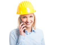 Casco d'uso dell'ingegnere femminile che parla al telefono fotografia stock