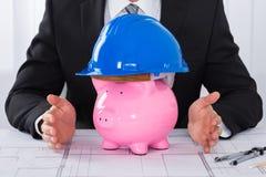 Casco d'uso della costruzione di Hands Protecting Piggybank dell'architetto Fotografie Stock Libere da Diritti