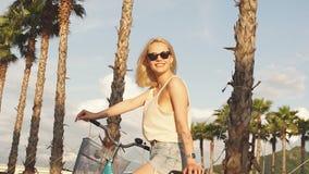 Casco de la bici - mujer que pone el casco biking en exterior durante paseo de la bicicleta almacen de metraje de vídeo