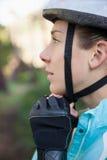 Casco de la bicicleta del motorista femenino de la montaña que lleva Imágenes de archivo libres de regalías