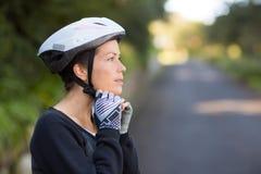 Casco de la bicicleta del motorista que lleva femenino Imagen de archivo libre de regalías