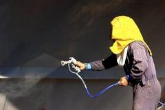 Casco de la nave de la pintura del trabajador usando el aerógrafo Fotografía de archivo libre de regalías