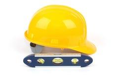Casco de la seguridad en el trabajo y nivel del agua amarillos Imagen de archivo