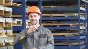Casco de protección que lleva sonriente del trabajador profesional de la industria que sonríe a la cámara almacen de video