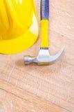 Casco de protección y martillo de garra amarillos en el vintage de madera Fotografía de archivo libre de regalías