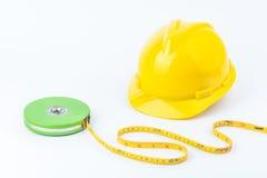 Casco de seguridad amarillo y cinta métrica verde Imagen de archivo