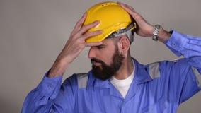 Casco de seguridad barbudo del tacto del ingeniero con las manos en fondo gris almacen de video