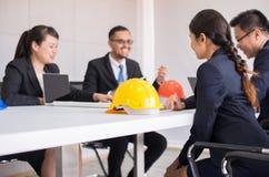 Casco de seguridad de los cascos en la sala de reunión, Blured del arquitecto de la gente y del ingeniero en la oficina fotografía de archivo libre de regalías
