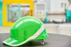 Casco de seguridad verde en fondo industrial Imágenes de archivo libres de regalías