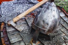 Casco del hierro en armadura y hacha Imágenes de archivo libres de regalías