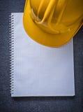 Casco della costruzione del taccuino sul concep nero della costruzione del fondo Immagine Stock
