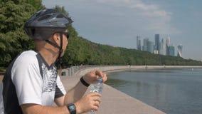 Casco di riciclaggio dell'uomo di mezza età, occhiali da sole d'uso, acqua potabile da una bottiglia stock footage