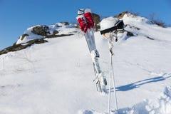 Casco ed occhiali di protezione con gli sci e Pali su Hillside Fotografia Stock Libera da Diritti