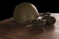 Casco, granadas de mano y balas militares en la tabla Imagenes de archivo