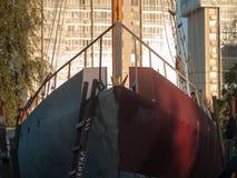 Casco grande del yate cerca del edificio alto imagen de archivo