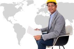 Casco masculino del amarillo del desgaste del ingeniero con el mapa del mundo Imagen de archivo