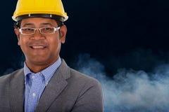 Casco masculino del amarillo del desgaste del ingeniero con humo Foto de archivo libre de regalías