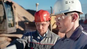 Casco masculino y vidrios que llevan del ingeniero de construcci?n del primer dos que discuten el trabajo metrajes