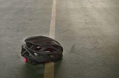 Casco negro de la seguridad para la bicicleta de ciclo en piso del deporte del gimnasio Fotografía de archivo
