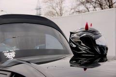 Casco nero del motociclo con i corni rosa sul tetto dell'automobile con un autoadesivo della bici di signora fotografia stock libera da diritti