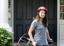 Casco que lleva del adolescente mientras que descansa sobre el ne de la bicicleta al aire libre Foto de archivo libre de regalías