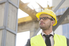 Casco que lleva del arquitecto de sexo masculino joven que mira lejos el emplazamiento de la obra Fotografía de archivo