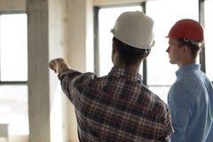 Casco que lleva del empleado que muestra el lugar de la construcción a un supervisor fotos de archivo libres de regalías