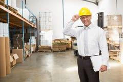 Casco que lleva del encargado de Warehouse que sostiene el tablero Imagenes de archivo