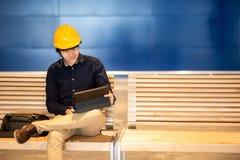 Casco que lleva del hombre asiático joven del ingeniero que trabaja con la tableta Imagen de archivo