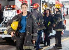Casco sicuro della tenuta di Firewoman mentre immagini stock