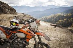 Casco sucio del motocrós de la motocicleta del enduro en el camino imagen de archivo