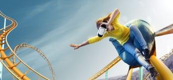 Casco usado VR de la realidad virtual de la mujer joven Ella ve el parque de la montaña rusa Fotografía de archivo