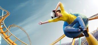 Casco usado VR de la realidad virtual de la mujer joven Ella ve el parque de la montaña rusa Imagen de archivo