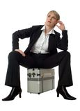Case. Young business women sitting on silver case waiting on white Royalty Free Stock Images