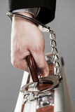 Case attached to hand with handcuffs Stock Image