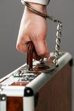 Case attached to hand with handcuffs Royalty Free Stock Images