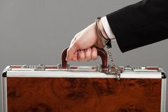 Case attached to hand with handcuffs Royalty Free Stock Image