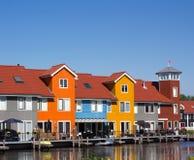 Case colorate con il pilastro vicino ad acqua fotografia stock