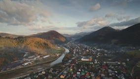 Case del villaggio al fiume d'avvolgimento della montagna ed alle foreste verdi archivi video