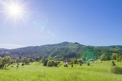 Case del villaggio sulle colline con i prati verdi nel giorno di estate Fotografia Stock Libera da Diritti