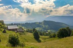Case del villaggio sulle colline con i prati verdi nel giorno di estate Fotografia Stock